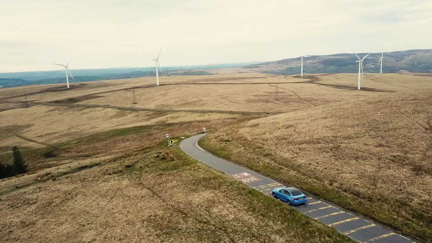 Drone footage of fast car driving along stunning scenery