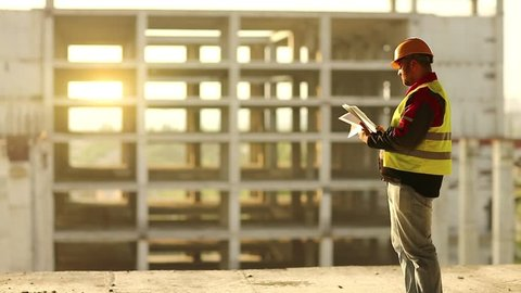 Master builder looks at new construction site and makes notes in works documentation. Worker in hard hat stands on project site and looks at new building structure, beautiful sunset at background