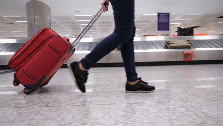 Passenger woman walk with trolley case against baggage carousel, low half view of slender female legs and medium wheeled bag, smooth tracking shot. Luggage conveyor belt number nine seen on background | Shutterstock HD Video #33313939