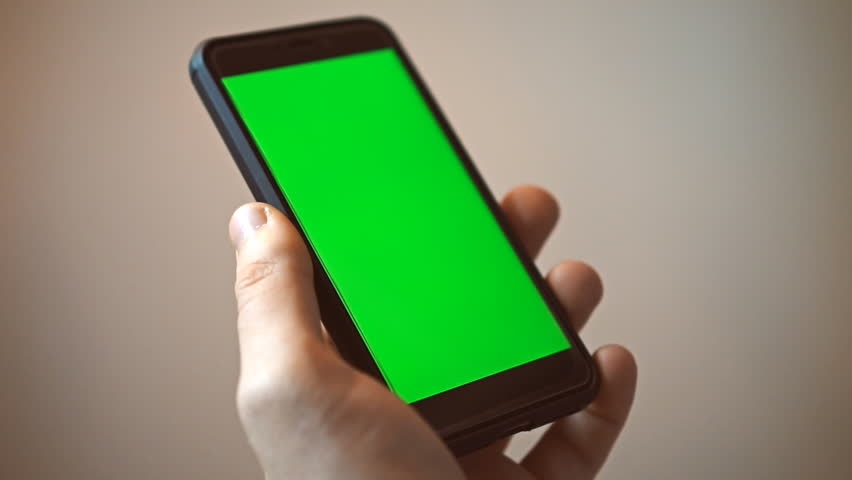 Hand holding mobile phone with green screen. Chroma key. #33345709