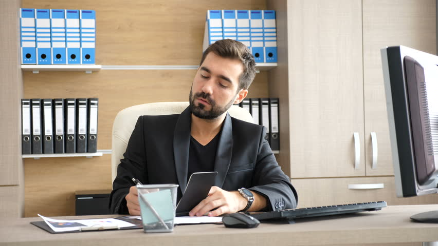 Young businessman in his office taking notes in a paper notebook. Modern business interior. Businessman in dressed semi informal | Shutterstock HD Video #33357409