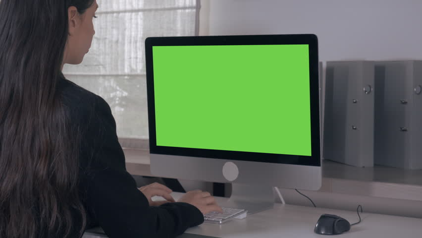 Back view woman with long hair sitting in front of display computer with green screen. unrecognizable female works at home or in office | Shutterstock HD Video #33402181