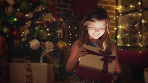 Girl ten years surprised by a Christmas gift. Magical bright light from the box