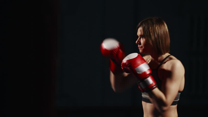 Brunette In Sport Suit And Boxing Gloves On A Black Background Conducts Training Punches The