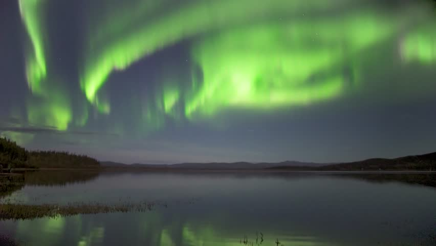 Real time (not a timelapse) strong green and pink aurora borealis (northern lights) dancing over lake in Alaska with realistic movement | Shutterstock HD Video #33431059