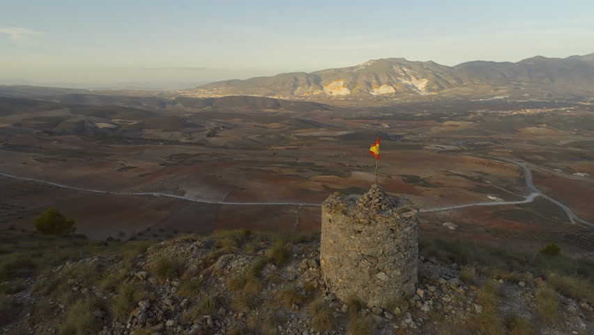 Circling Flight Around an Abandoned Spanish Watchtower With a Flag Flying and Beautiful Surrounding Mountainous Landscape
