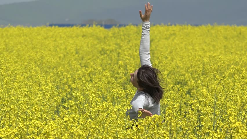 Young woman dancing in blossom rape field, feel the beauty of nature, sun rays caress girl smiling face, wind play with woman hair, feel nature joy