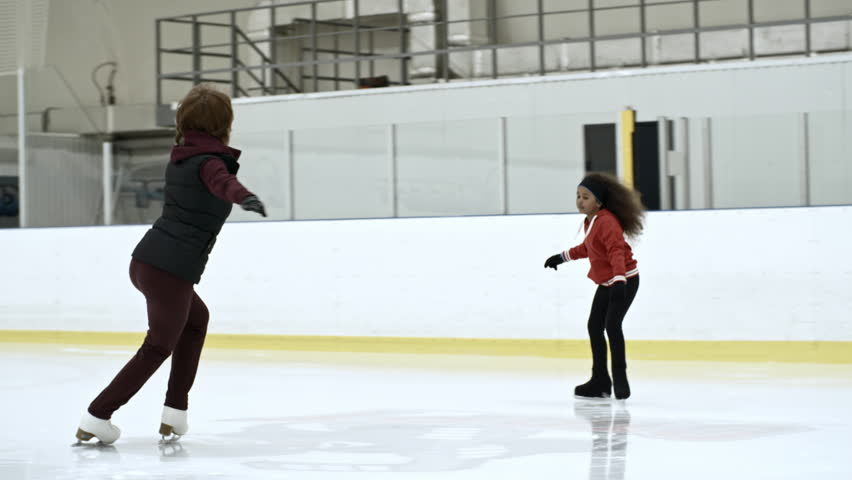 Little African girl training figure skating on ice rink with experienced female coach