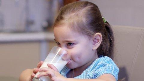 Little child girl drinking a milk at kitchen. 4K UltraHD video