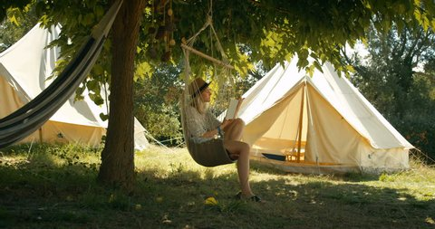 Beautiful Young Woman Reads Book while Sitting in the Hammock Chair under the Tree. Girl Wears a Hat, in the Idyllic Background with Green Trees and Camping Tents. Shot on RED Epic 4K Camera.