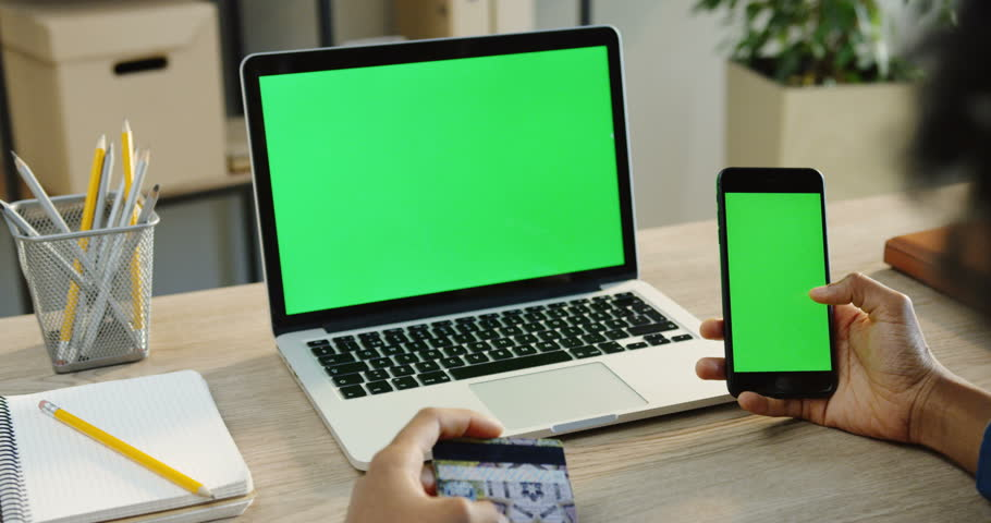 Over shoulder view on the African American male hands scrolling on a black smartphone with green screen and holding a credit card while doing online shopping. Laptop computer with green screen on the #33502879