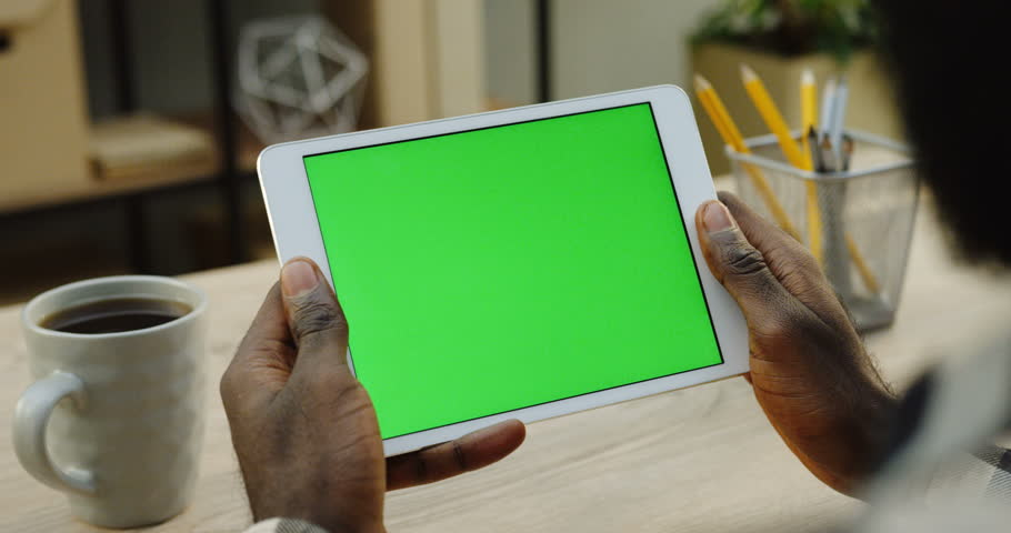 Over shoulder view on the white tablet computer holded by african american man horizontally. Fingers scrolling and taping on it. Green screen. Chroma key. Wooden office desk with cup of coffee | Shutterstock HD Video #33502930