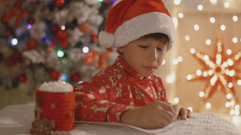 Dreamy boy in pajamas and santa hat writing the letter to Santa with the cup of cocoa with marshmallow