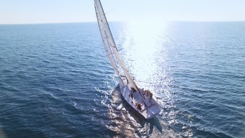 Aerial footage from drone, of professional speed yacht or sailboat leaning to one side, ready to make a maneuvre, wind in mainsail attached to mast, team race or competition, with sun flares