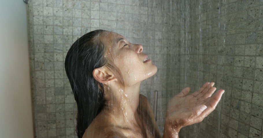 Shower Woman, Young woman showering washing in hair in hot water in luxury bathroom. Happy adult relaxing enjoying luxury bathtime cleaning her face and rinsing her body at home. Mixed race model.
