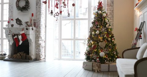 4K video footage of white room with Christmas and New Year interior decoration. Green tree decorated with toys and flashing garland