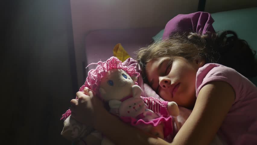 Adorable little girl night sleep in the sofa bed and hug her baby doll. girl brunette teenager indoors cute asleep on the bed