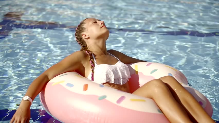 Beautiful young woman relaxing in swimming pool. Girl in outdoor pool at luxury hotel with inflatable rubber circle