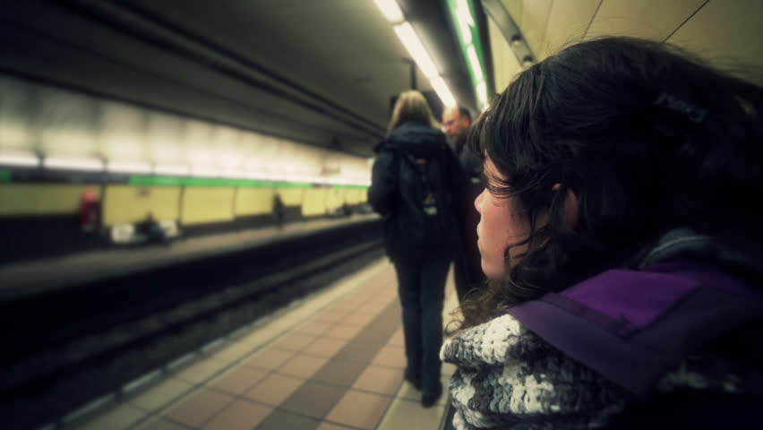 Woman seated waiting for the arrival of the metro