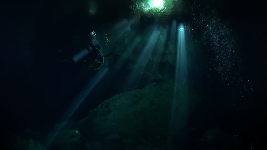 Swimming with flashlight in dark caves of Yucatan cenotes underwater in Mexico. Natural landscape in clean and clear underground water. Unique scuba, diving