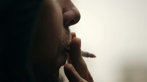 Closeup shot of a man's face who smoking a cigarette.