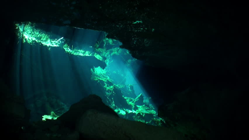 Yucatán caves of cenotes underwater in Mexico. Scuba diving in clean and clear underground water in reflection sunlight.