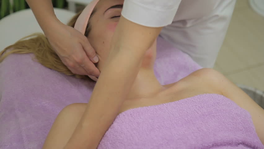Masseur makes massage of neck and decollete of woman in clinic. Female massages gently delicate skin of neck of young client and then moves smoothly into naked decollete zone. Specialist dressed in