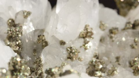MACRO DOF: White quartz with metallic pyrite particles shining like ice under bright lights. Glimmering opaque quartz with metallic pyrite creating a beautiful image. Lavish precious stones glittering