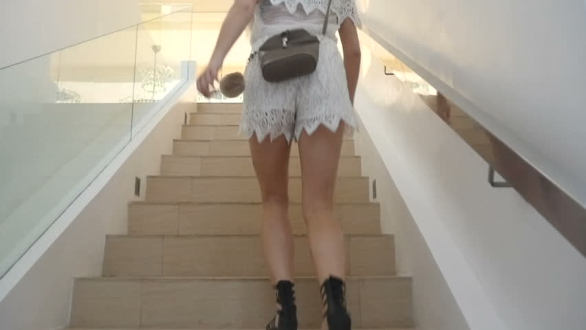 Rear view of young attractive woman going up the stairs indoors
