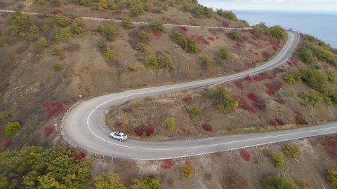 White crossover car goes on serpentine mountain road. Aerial view. Drone is following vehicle.