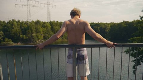 Young Adult jumps off a high bridge into beautiful lake in sunny summer in 4k super slow motion
