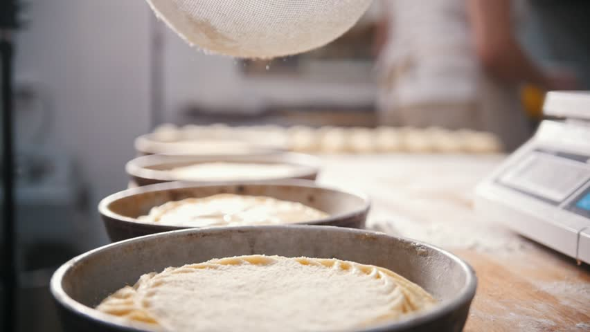 Cook sifts flour and sugar decorating pies in the bakery