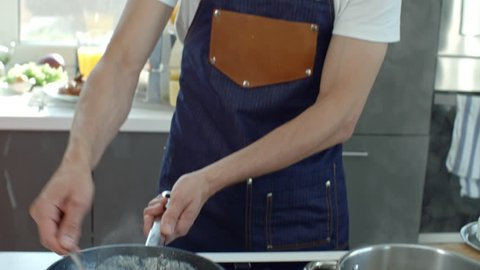 Handheld shot of male professional chef in apron talking and stirring bacon frying in cream sauce in hot pan while cooking in kitchen