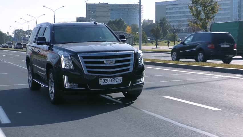 MINSK, BELARUS - AUGUST 20, 2017: Black new shiny Cadillac Escalade 6.2 V8 drives on a road on a sunny day. Escalade is a full-size luxury SUV, most most identifiable model of Cadillac.