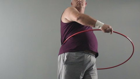 Obese male trying to twist hula hoop, dreams of healthy and fit body, weightloss