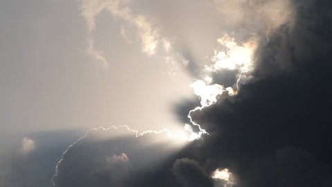 Looking up toward the sun. Sunbeams breaking trough the clouds.