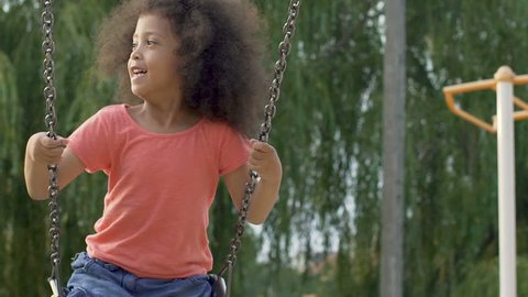 Cute black girl having fun, swinging up and down in yard, carefree childhood