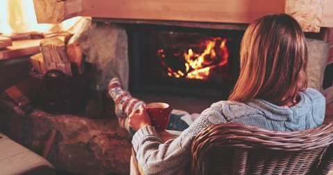 Woman relaxes by warm fire with a cup of hot drink and warming up her feet in woollen socks. Feet in woollen socks by the Christmas fireplace. Cozy atmosphere. Winter and Christmas holidays concept.