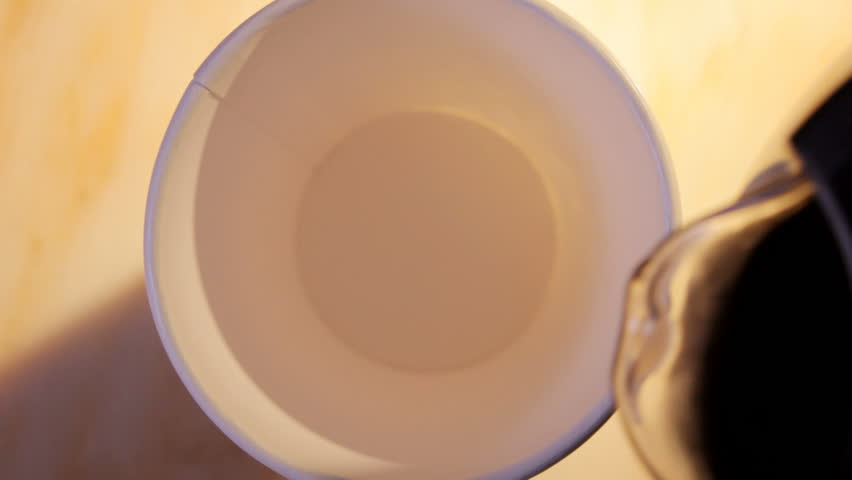 close up HD video of coffee and milk pouring into paper cup, hand takes cup away from right side.