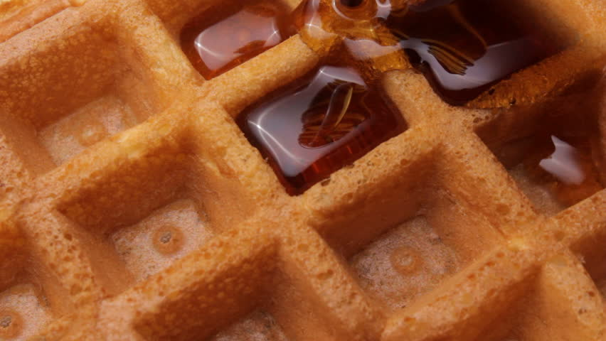 Pouring maple syrup on a waffle