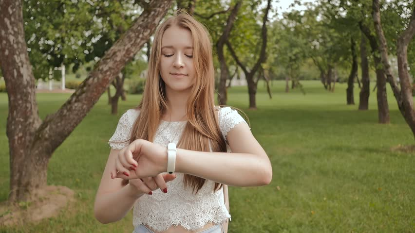A young girl is engaged in a walk in the park, looking at a smart clock on her arm and receiving a pulse measurement. Health. Sport. Recreation. Summer.