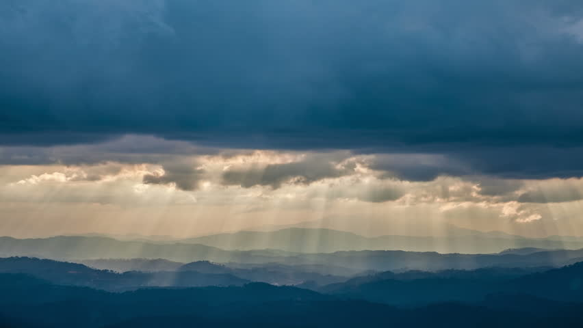 Time Lapse. Sun rays pass through the clouds over the mountains.