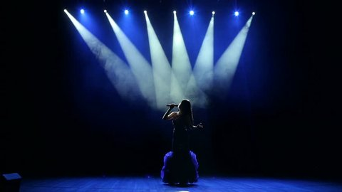 Silhouette of a beautiful girl on stage with concert lighting in a beautiful evening dress. The beautiful singer sings on stage in the dark.