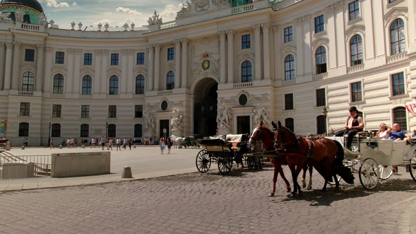"A viennese Coach, so called ""Fiaker"" passes by at the Michaelerplatz at this wide angle shot of the ""Wiener Hofburg"", Sky is replaced.  Variation without: ""Vienna Hofburg  with Fiaker - tilt up""."