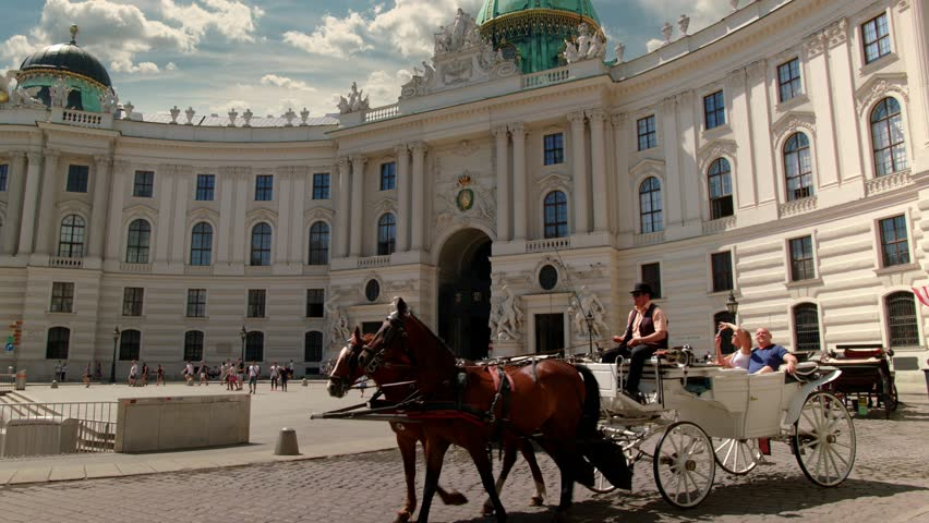 """A viennese Coach, so called """"Fiaker"""" passes by at the Michaelerplatz at this wide angle shot of the """"Wiener Hofburg"""", Sky is replaced.  Variation without: """"Vienna Hofburg  with Fiaker - tilt up""""."""
