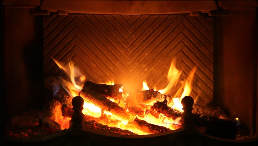 Round Logs Burn In Fireplace Stock