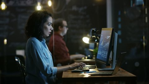 Stressed, Overworked Female Financier Holds Her Head in Hands while Working on a Personal Computer. In the Background Creative Office.