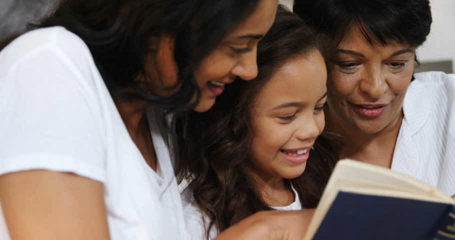 Multi-generation family reading a book in bedroom at home 4k