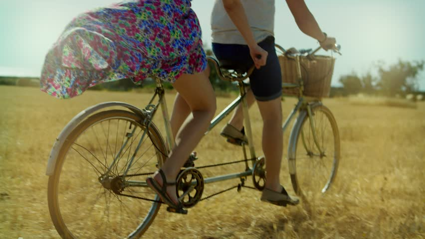 Young man and woman riding a bicycle tandem on rural field and haystacks
