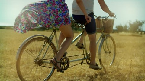 Young man and woman riding a bicycle tandem on rural field and haystacks. Couple woman and man cycling bike tandem on summer field on background nature landscape